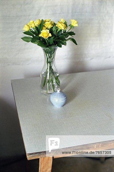 Vase aus Glas mit gelben Rosen auf einem Tisch - Blumen