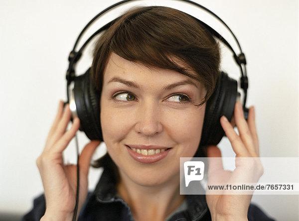 Junge  dunkelhaarige Frau hört Musik über einen Kopfhörer (Portrait)