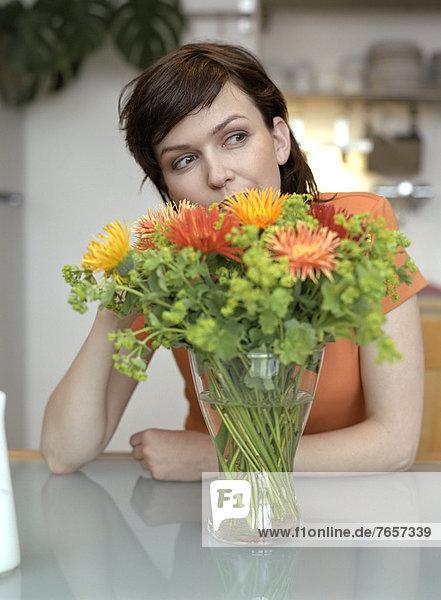 Junge  dunkelhaarige Frau hinter Blumenstrauß