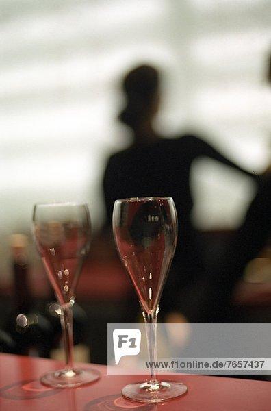 Zwei leere Sektgläser  im Hintergrund die Silhouette einer Frau