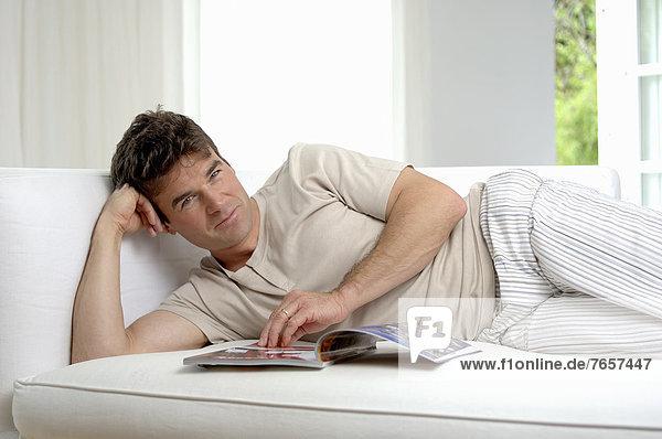 Mann liegt auf dem Sofa und blättert in einer Zeitschrift