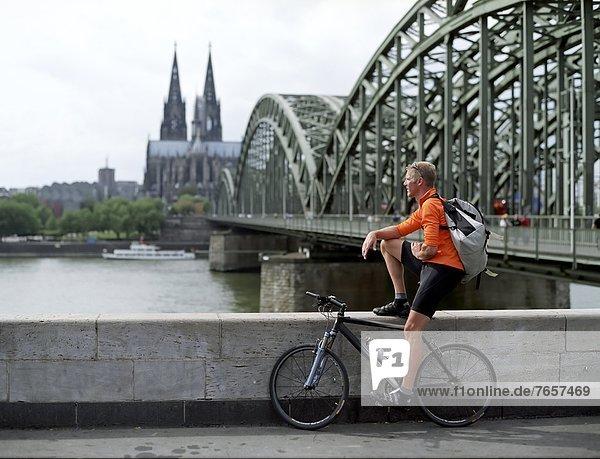 Köln  Fahrradkurier macht Pause und blickt auf den Rhein nahe einer Brücke