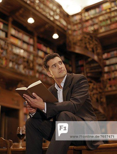 Mann sitzt in einer Bibliothek und liest ein Buch