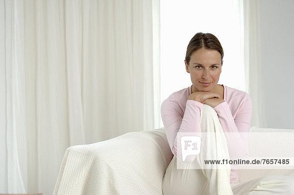Frau auf einem weißen Sofa stützt das Kinn auf beide Hände