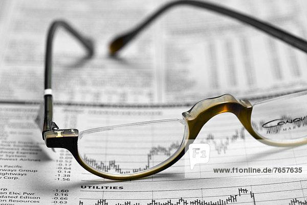 Brille liegt auf einem Börsenblatt