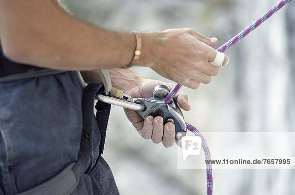 Person befestigt ein Kletterseil an der Taille - Ausrüstung - Nahaufnahme