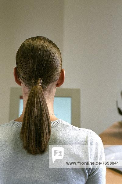 Brünette Frau sitzt vor Computer - Information - Arbeitsamt