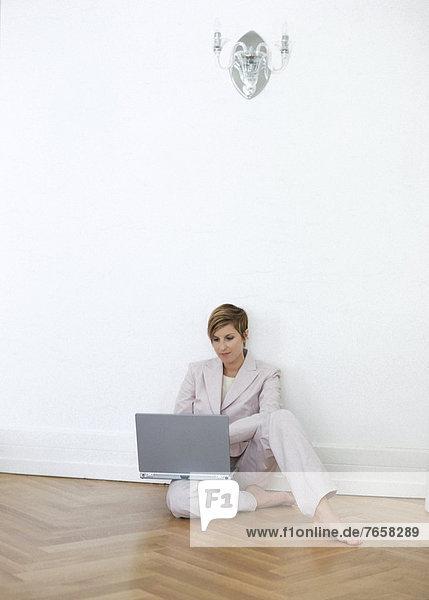 Blonde Geschäftsfrau mit Laptop (auf Boden sitzend)