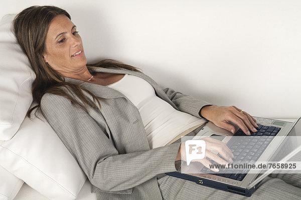 Reife Geschäftsfrau  die auf der Couch liegt und auf dem Laptop tippt.