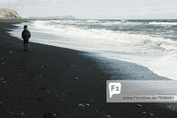 Junge  der am Strand spazieren geht und den Horizont beobachtet  Island