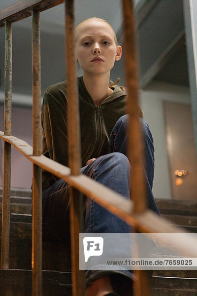 Junge Frau auf der Treppe sitzend  durch das Geländer schauend