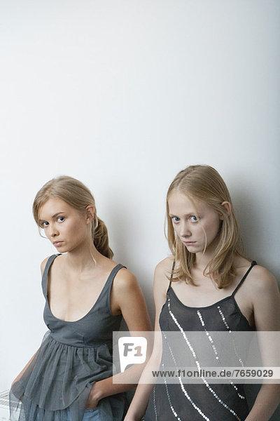 Junge Frau und Teenagerin lehnen sich an die Wand und schauen vorsichtig in die Kamera.