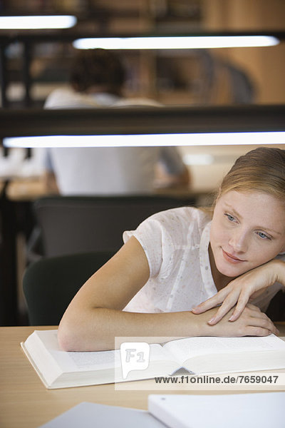 Young woman daydreaming while studying