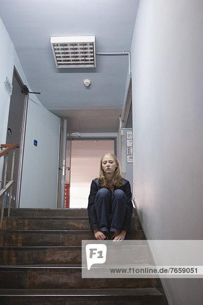 Junge Frau allein auf der Treppe sitzend