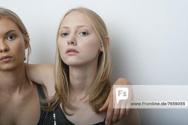Junge Frau mit Arm um die Schulter der Freundin  Portrait
