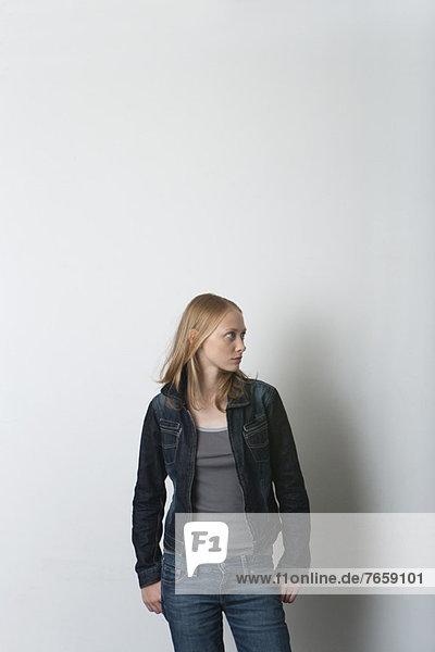 Junge Frau stehend mit Händen in den Taschen  wegschauend