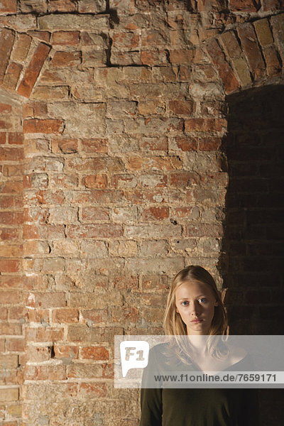 Junge Frau vor Backsteinmauer  Portrait
