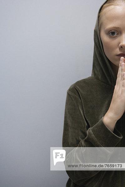 Junge Frau mit im Gebet umklammerten Händen  abgeschnitten