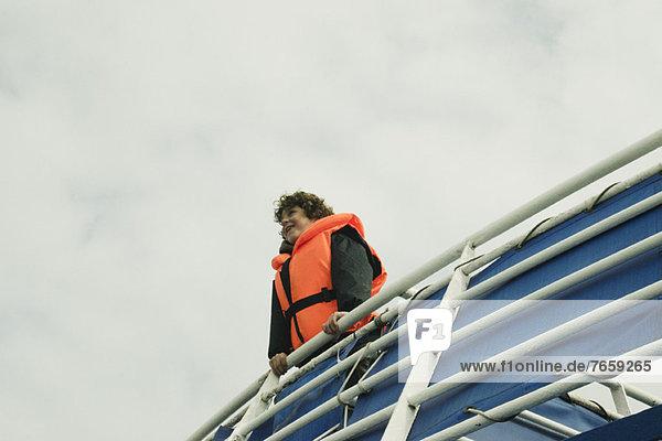 Junge lächelndes Gesicht am Horizont,  auf dem Oberdeck eines Bootes