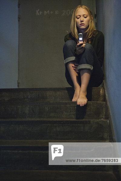 Junge Frau sitzt allein auf der Treppe und schaut auf das Handy.