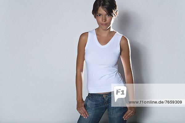 Junge Frau stehend mit Händen in den Taschen  Portrait