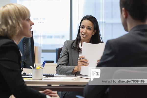 Geschäftspartner im Gespräch  Fokus auf Geschäftsfrau im Hintergrund