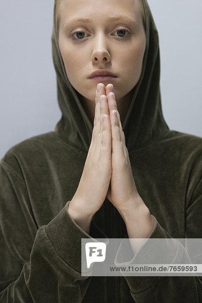 Junge Frau mit im Gebet umklammerten Händen  Porträt