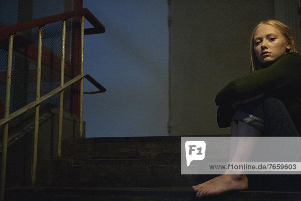 Junge Frau auf der Treppe sitzend  Knie umarmend