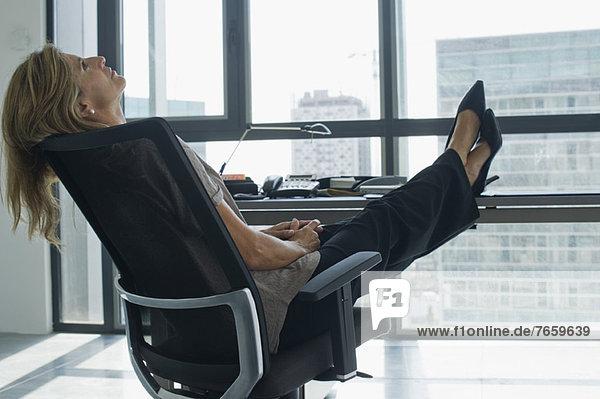 Geschäftsfrau lehnt sich im Stuhl zurück und steht mit den Füßen auf dem Schreibtisch. Geschäftsfrau lehnt sich im Stuhl zurück und steht mit den Füßen auf dem Schreibtisch.
