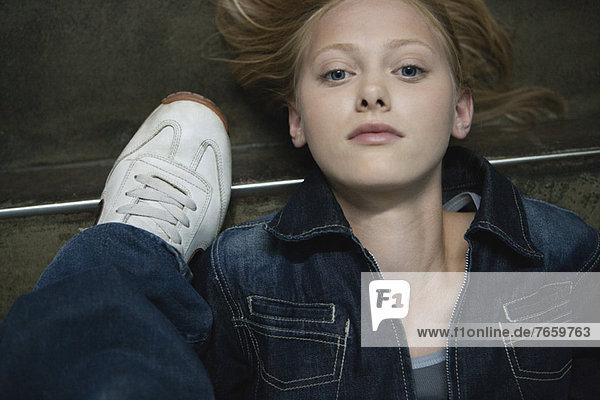 Junge Frau auf dem Boden neben einem Schuh liegend  Portrait