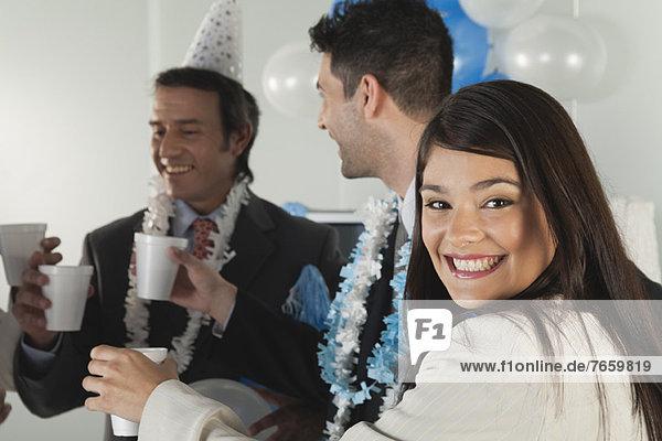 Junge Frau beim Trinkspruch mit Kollegen bei der Bürofeier