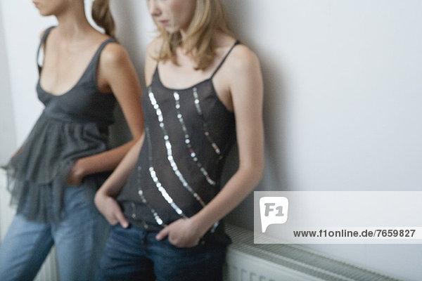 Junge Frau und Teenagermädchen an der Wand lehnend  beschnitten