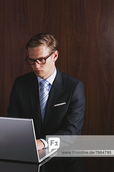 Businessman with glasses using laptop
