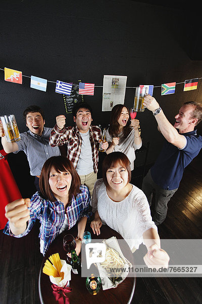 Young people cheering in a bar