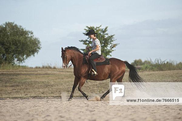 Frau galoppiert auf einem Quarter Horse