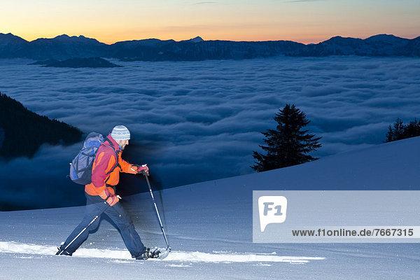 Ein Mann beim Schneeschuhwandern  Schneeschuhwanderung am Ahornkaser an der Rossfeldstraße  Blick zum Watzmann  Berchtesgadener Land  Bayern  Deutschland  Europa