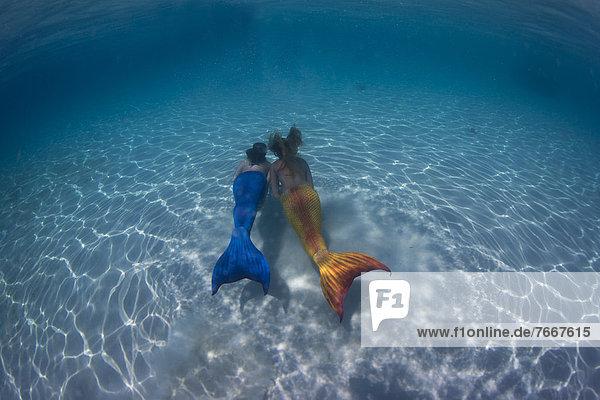 Mermaids  girls wearing mermaid costumes swimming in the shallow water of a lagoon  underwater