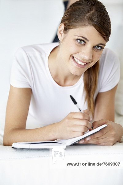 Portrait of young woman writing in notepad