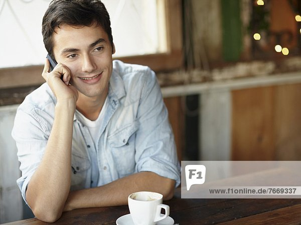Young man sitting in cafe and talking on cell phone
