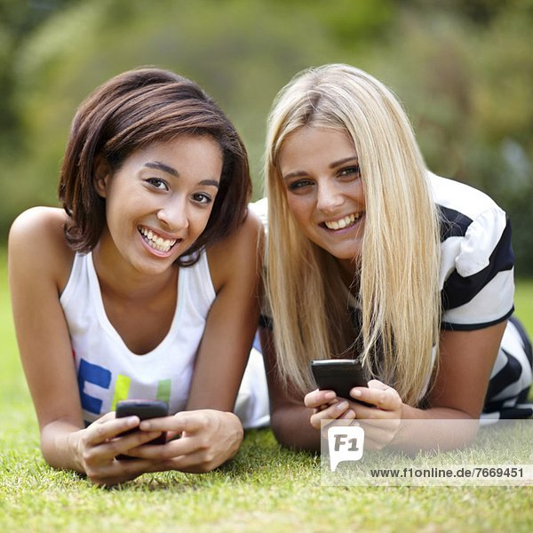 Portrait of young women lying on grass  using mobile phone