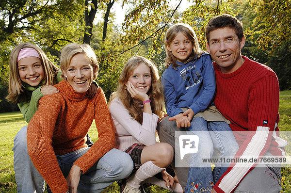 Familie  Vater  Mutter  drei Töchter  im Park