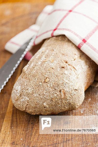 Frischer Brotlaib und Küchenmesser auf einem Holzbrett