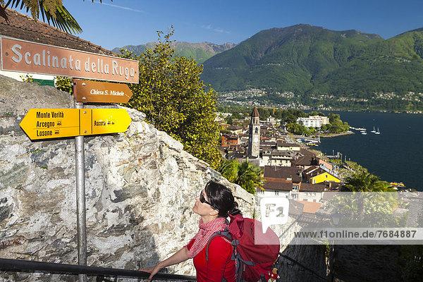 Eine Frau beim Wandern  betrachtet einen Wegweiser  Ascona  Lago Maggiore  Tessin  Schweiz  Europa Eine Frau beim Wandern, betrachtet einen Wegweiser, Ascona, Lago Maggiore, Tessin, Schweiz, Europa