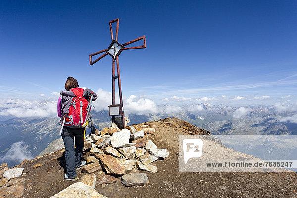 Bergsteiger am Gipfelkreuz auf dem Schneebiger Nock in der Rieserfernergruppe  Südtirol  Italien  Europa