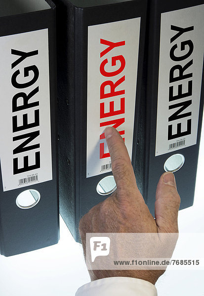Hand pointing to a ring binder labeled Energy  symbolic image