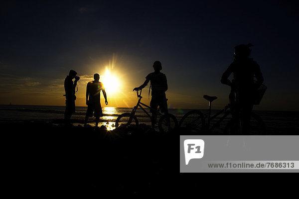 Ein Fahrradfahrer  ein Mann mit Kamera und Badegäste bei Sonnenuntergang am Strand  in Playa de las Américas  Teneriffa  Kanarische Inseln  Spanien  Europa