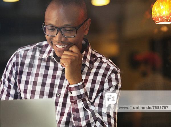 Smiling man reading laptop indoors