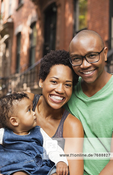 Familie lächelt gemeinsam auf der Stadtstraße