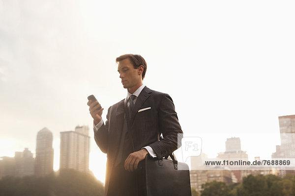 Geschäftsmann mit Handy im Stadtpark