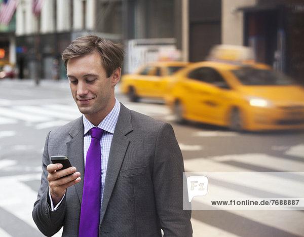 Geschäftsmann mit Handy in der Stadtstraße